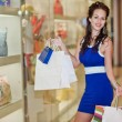 Photo of young joyful woman with shopping bags on the background of shop windows — Stock Photo