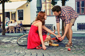 Man fell down from the bicycle and woman help him to collect products — Stock Photo