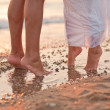 Legs of kissing couple on beach - Stock Photo