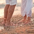 Legs of kissing couple on beach — Stock Photo