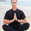 Young man doing yoga on the beach — Stock Photo #26444349