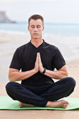 Young man doing yoga on the beach — Stock Photo