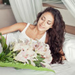 Womwith beautiful flowers in bed — Stock Photo #26607127