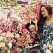 Beautiful young woman buying flowers at market — Stock Photo