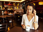 Beautiful Woman Drinking Coffee and talking on cellphone — Stock Photo