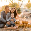 Happy family with pumpkin on autumn leaves. Outdoor. — Stock Photo