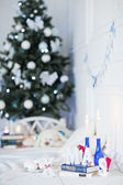 Decorated Christmas tree and gift, candles, pillows in room — Stockfoto