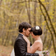 Kissing bride and groom in their wedding day near autumn tree in the forest — Stock Photo
