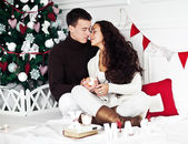 Young couple under new year tree — Stock Photo