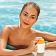 Girl putting sun block near pool holding white sun tan lotion bottle — Stock Photo