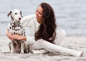 Young woman with dog on the beach — Stock Photo