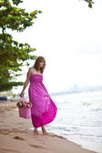 Young woman in pink dress resting on beach in Thailand — Stock Photo