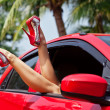 Legs showing from red car. — Stock Photo #34256021