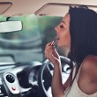 Woman is doing makeup on the run in her car — Stock Photo #34256391