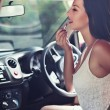 Woman is doing makeup on the run in her car — Stock Photo #34256439