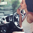 Woman is doing makeup on the run in her car — Stock Photo