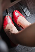A woman's foot depressing the brake pedal of a car. — Stock Photo
