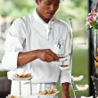 Asian chef laying a table with luxury food and drinks on wedding. — Stock Photo