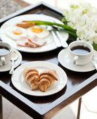 Breakfast with cup of black coffee, eggs and croissants on balcony — Stock Photo