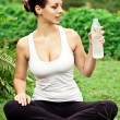 Spiritual fit woman sitting in lotus pose and drink water — Stock Photo