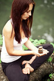 Spiritual fit woman sitting in lotus pose on a river stone — Stock Photo