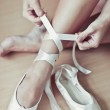Ballet dancer tying slippers around her ankle woman ballerina pointe — Stock Photo