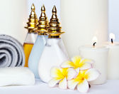 Three Plumeria flower with massage oil and balsam in bowl , towel and candle — Stock Photo