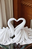 Towel swans left by a hotel room service — Стоковое фото
