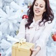 Happy young woman giving christmas present box — Stock Photo