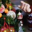 Young pretty woman decorate new year tree with christmas toys — Stock Photo #37561433