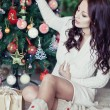 Young pretty woman decorate new year tree with christmas toys — Stock Photo #37561687