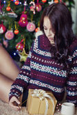 Young pretty woman under new year tree with christmas present — Stock Photo