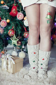 Woman's leg under new year tree with christmas present — Stock Photo