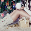 Stock Photo: Young pretty womunder new year tree with christmas cup of tea