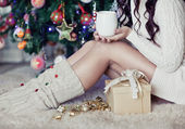 Young pretty woman under new year tree with christmas cup of tea — Stock Photo