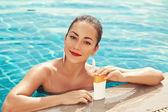 Girl putting sun block near pool holding white sun tan lotion — Stock Photo
