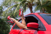 Legs showing from red car. — Stock Photo
