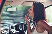 Beautiful woman doing makeup in the car — Foto de Stock
