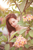 Young woman with tropical flower Plumeria alba — Stock Photo