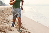 Young athletic man exercising and running on the beach — Stock Photo