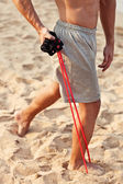 Young athletic man exercising and doing fitness with a chest expander(resistance band ) on the beach — Stock Photo