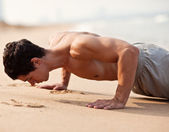Fitness man exercising push ups. Male fitness model cross-training on beach. Caucasian man in his twenties. — Stock Photo