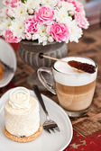 Coconut pastry with flowers, latte and chocolate croissant — Stock Photo