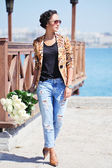 Beautiful woman in jeans and jacket just received a bouquet of white roses. — Photo