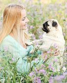 Cute blond girl having fun with her dog at the park — Stock Photo