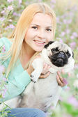 Cute blond girl having fun with her dog at the park — Stock fotografie