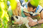Cute couple having fun with their dog at the park — Stock fotografie