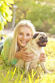 Cute blond girl having fun with her dog at the park — ストック写真