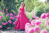 Pregnant woman in blooming garden of peony — Stock Photo