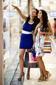 Photo of young joyful girls with shopping bags on the background of shop windows — Stock Photo